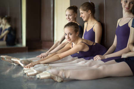 Five young dancers in the same dance costumes, resting sitting on the floor. Dance Class. Ballet School. Discussions yet with each other. One model looks to the camera. Stock Photo