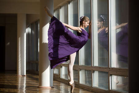 ballerina: Graceful ballerina dancing in a purple dress leg lifted high, standing on pointe near a large window in the setting sun. Stock Photo