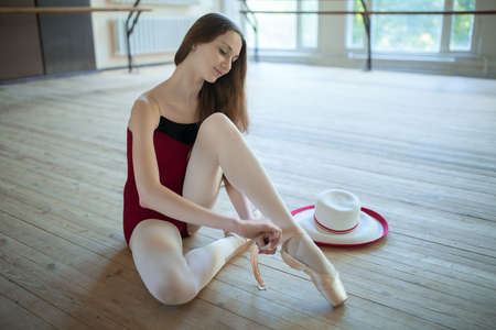 ballerina costume: Young ballerina sitting on the floor dance classroom gently tying pointe. Beside her on the floor is a long-skirted hat, costume attribute.