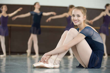 ballerina with smile sitting on the floor in a dance class dancers practicing on the background Zdjęcie Seryjne
