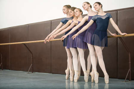 Five ballet dancers in class near the barre. Model wearing white tights. Girls look toward