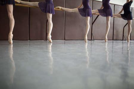zapatillas ballet: Cinco bailarines de ballet en clase cerca de la barra, sólo las piernas. Con medias blancas Modelo, con un pie apoyado en la barra