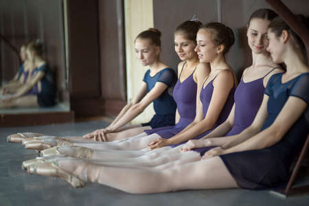 leotard: Five young dancers in the same dance costumes, resting sitting on the floor. Dance Class. Ballet School. Discussions yet with each other.