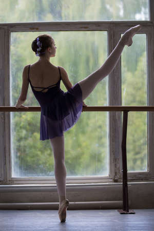 Young ballerina standing on one leg on your toes in pointe and doing stretching, lifting the leg up high. Model holds hands behind the barre.