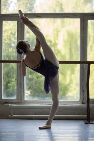 barre: Young ballerina standing on one leg on your toes in pointe and doing stretching, lifting the leg up high. Model holds hands behind the barre.