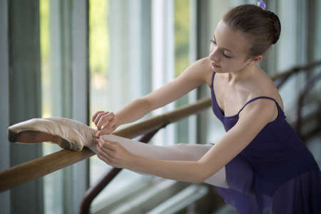 Young ballerina standing near the window, tying ribbons of pointe shoes in the slope. Putting your foot on the barre.