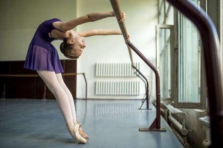 bailarina: Bailarina joven que hace ejercicio en el aula cerca barre. Estirar la espalda. Modelo descansa en las manos de la barra.