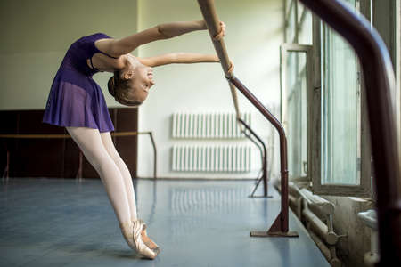 ballet dancer: Young dancer doing a workout in the classroom near barre. Stretching back. Model rests in the hands of the barre. Stock Photo