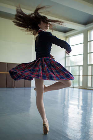 spins: Long-haired ballerina spins in the dance moves on one leg to stand on pointe.