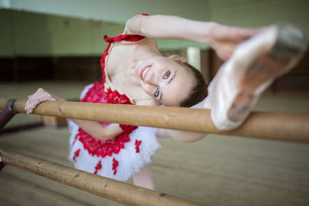 choreographic: Portrait of a ballerina that makes stretching the legs near the choreographic crossbar. Girl makes the slopes. Looking at the camera with a sweet smile.