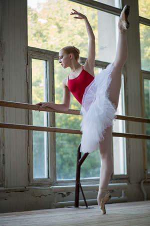 Young ballerina standing on one leg on your toes in pointe and doing stretching, lifting the leg up high. Model holds hands behind the barre. Zdjęcie Seryjne - 37819063