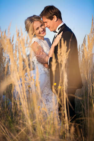 Young wedding couple standing in a field of pigweed in the setting sun. Newlyweds hug with a smile. Фото со стока