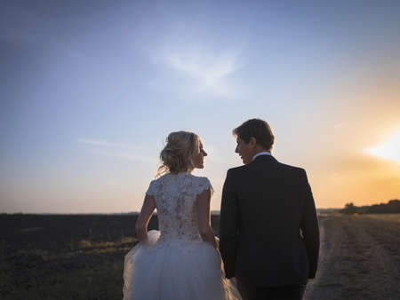 newlywed couple: Young wedding couple talking on the field at sunset. Newlyweds back to Kemer look at each other.