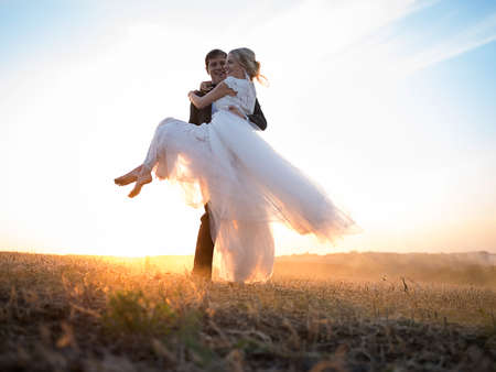 Husband carries his beloved wife in his arms, in the setting sun. Couple dressed in elegant wedding clothes. Travel along the ground on sunset haze. Banco de Imagens