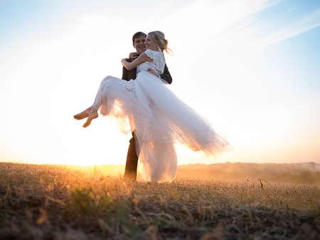 Man draagt zijn geliefde vrouw in zijn armen, in de ondergaande zon. Koppel gekleed in elegante bruiloft kleding. Reis langs de grond op zonsondergang waas.