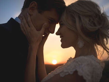 wife: Close portrait silhouette in love wedding couple. Against the setting sun in the field. Lovers hug, girl tenderly holding her husbands face with both hands, smiling and looking into his eyes.