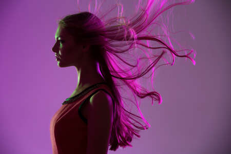 flying hair: Studio profile portrait of long-haired girl in bright pink background with flying hair in the wind.