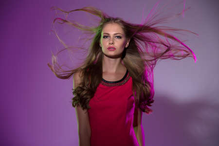 flying hair: Studio portrait of long-haired girl in bright pink background with flying hair in the wind.