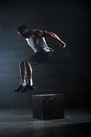 hombre deportista: Atleta dio ejercicio. Saltando en la caja. Touchdown Fase. Fotograf�as de estudio en el tono oscuro. Foto de archivo