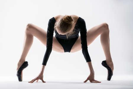 en cuclillas: Bailarina agraciada hacen estirando las piernas muy separadas en una posición en cuclillas sobre los dedos de los pies Foto de archivo