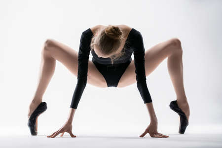 spreading: Graceful ballerina make stretching his legs wide apart in a squat on the toes