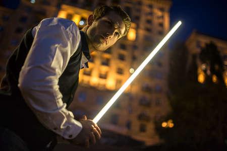 Handsome guy holding a lightsaber Jedi. Twilight in the Ukrainian capital Kiev.