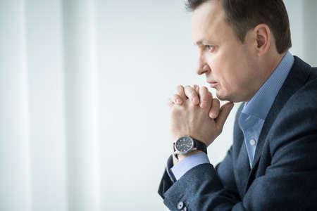 hombre pensando: Hombre de negocios atractivo sentado pensativo mirando por la ventana apoyó la barbilla. Foto de archivo