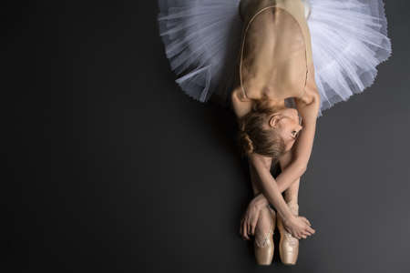 ballerina: Young, graceful ballerina sitting on the floor on a black background in a studio in the slope face touching knees. Close-up. Stock Photo