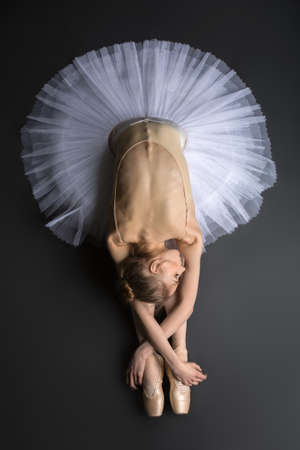 Young, graceful ballerina sitting on the floor on a black background in a studio in the slope face touching knees. Close-up. Foto de archivo