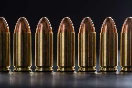 Number pistol cartridge 9 mm caliber on a black background photo