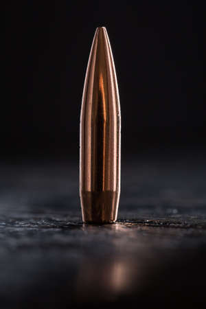 caliber: One copper bullet with bright reflections on a black background Stock Photo