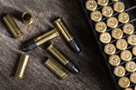 Scattering of small caliber cartridges on a wooden background. Other cartridges cartridges lies in capsules up. The picture from the top point. Foto de archivo