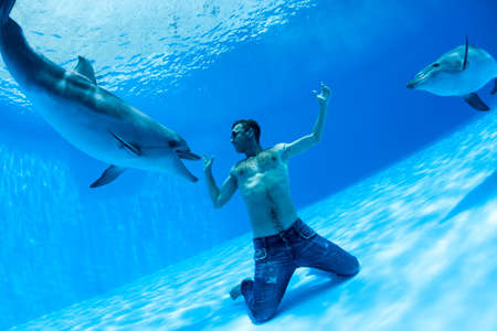 dolphinarium: Men and two dolphin fooling around on the bottom of the dolphinarium