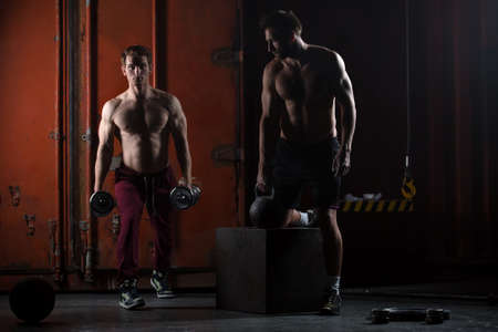 kettlebell: Two beautiful athlete train. One does kettlebell swings, squats with dumbbells other. The picture in the studio in a dark tone.