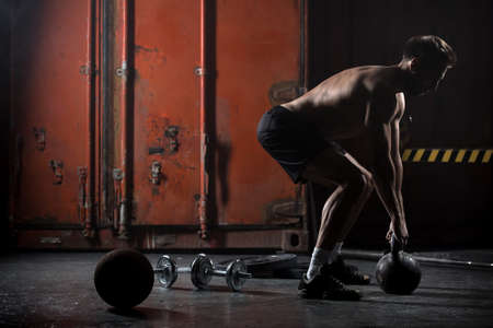 Beautiful athlete doing kettlebell swings. View from the back. Athlete bare-chested. Studio shot in a dark tone.