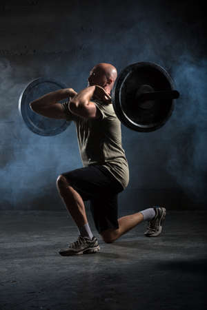 barbell: Bald athlete doing exercise with a barbell. Studio shot.
