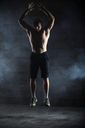topless: Bald athlete topless jumping up. The picture in the studio in the style of low-key.