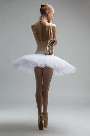 Portrait of young ballerina in white tutu is throwing his arm over her shoulder with pointe Zdjęcie Seryjne - 39766923