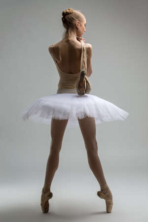 ballerina tights: Portrait of young ballerina in white tutu is throwing his arm over her shoulder with pointe