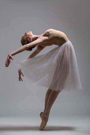 Graceful ballerina standing on toes bending the back. Studio shot. Foto de archivo