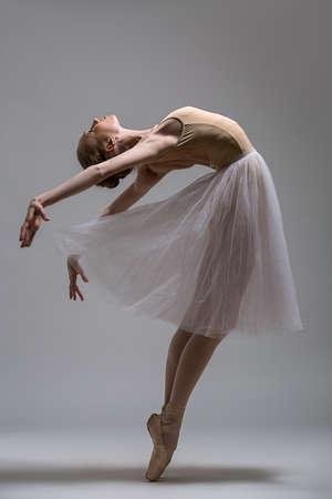 gimnasia: Bailarina agraciada de pie sobre los dedos del pie doblado la espalda. Estudio de disparo.