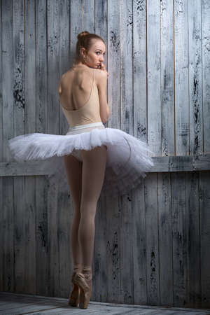 modest: Modest ballerina standing near a wooden wall on pointe in a tutu.