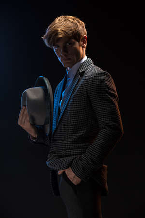 redheaded: Redheaded man in a plaid suit with hat in hand on a black background in the studio Stock Photo