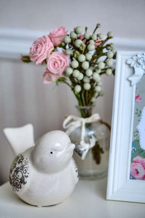 Close-up in the interior decor. Ceramic bird, photo frame and vase with flowers photo