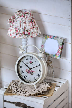 Bedside table with lamp and alarm clock. Home Decor. photo
