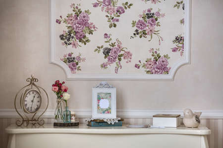 vase: Shelf with home decor in the style of provence, watches, flowers in a vase and photo frame.