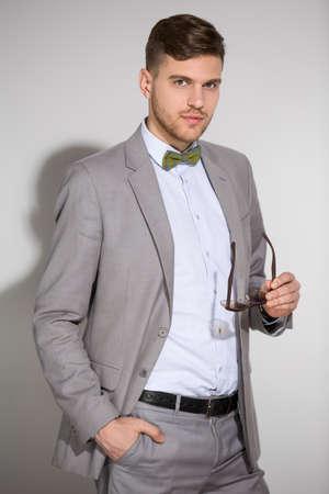 Attraktive Mann in Anzug und Krawatte Schmetterlingskleid stilvolle Sonnenbrille. Studio shot.