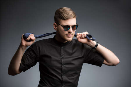 mirrored: Stylish man in black shirt and mirrored sunglasses, posing, playing with a tie. Studio shot.