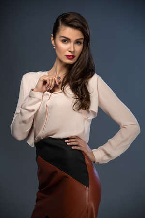 leather skirt: Portrait glamorous brown-haired business style girl dressed in a blouse and a leather skirt