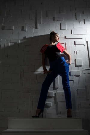 pantsuit: Fashion portrait of a girl in a designer pantsuit near textured wall in the studio. Stock Photo